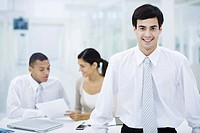 Businessman smiling at camera, colleagues working in background