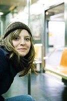 Young woman riding subway, smiling at camera (thumbnail)
