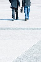 Two businessmen walking together wearing business attire, one wearing jeans with blazer