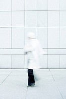 Woman wearing white coat, white knit hat and white knit scarf walking down sidewalk (thumbnail)