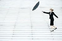 Businesswoman struggling with umbrella in wind