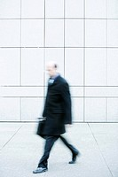 Businessman walking on sidewalk