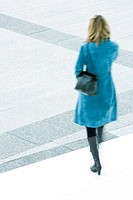 Woman in blue overcoat descending steps outdoors