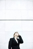 Businesswoman using cell phone, looking up