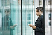 Businesswoman using cell phone, looking at camera