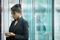 Businesswoman using cell phone, looking down