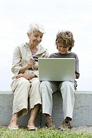 Grandmother and grandson using laptop outdoors, shopping online