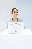 Woman standing behind pedestal with certificate on top of it, smiling at camera