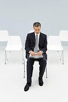 Businessman sitting in chair using laptop, empty chairs in background