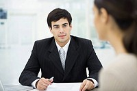 Businessman sitting at desk, listening to female client