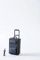 Miniature businessman facing large suitcase