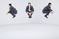Identical businessmen jumping in midair