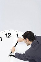 Businessman trying to turn back hands of clock (thumbnail)