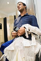 Teen boy holding clothing on hangers in store (thumbnail)