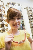 Teen girl holding sunglasses in store
