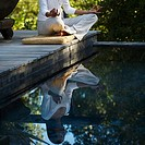 Woman meditating on dock