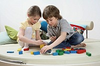 Brother and sister playing with toy blocks