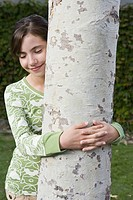Preteen girl hugging tree