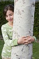 Preteen girl hugging tree