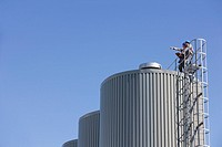 Workers on top of industrial silo