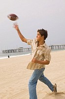 Teenage boy throwing football