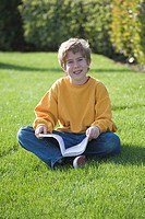 Boy sitting on grass holding book