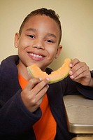 Boy eating cantaloupe