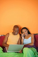 Couple in bed using laptop computer and cellular phone