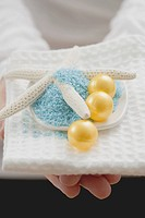 Young woman holding bath salts & bath pearls with starfish (thumbnail)