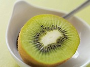 Half a kiwi fruit in bowl with spoon