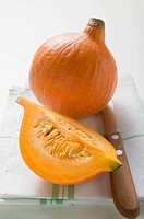 Hokkaido pumpkins whole and quarter on tea towel, knife (thumbnail)