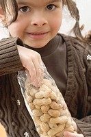 Girl reaching into a bag of peanuts