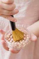 Girl holding powder pearls and brush