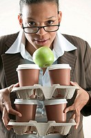 Businesswoman holding four cups of coffee and an apple