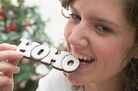 Woman biting Christmas biscuit the word HOHO
