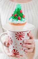 Woman holding cupcake on large mug Christmas