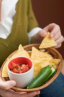 Woman holding basket of nachos with salsa and chilli