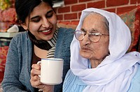 Elderly Sikh grandmother drinking tea while sitting with her granddaughter.