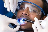 Close_up of dental professionals using ultraviolet light to treat on a male patient.