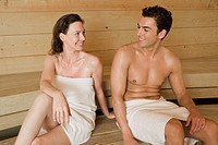 portrait of woman and man relaxing in sauna