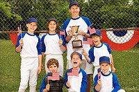 Young baseball team holding flags and trophy