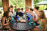 Teenagers eating cake at birthday party