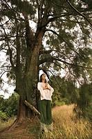 Woman doing yoga under tree