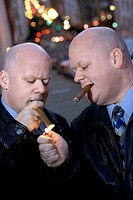 Identical twins smoking cigars