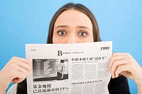 Young woman holding newspaper, close-up