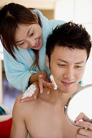 Young woman shaving young man, smiling, close-up