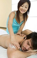 woman putting cream on man,s shoulder