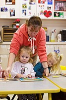 Teacher and children students work puzzles in daycare facility
