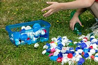 Child's hands selecting plastic screw caps