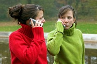 Portrait of two teenagers, twin sisters, calling with mobile phones